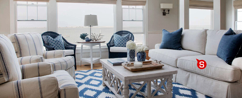 A Beach House style living room in whites, greys and blues. Patterned carpet, checkered cushions ad armchair upholstery complement the interior.