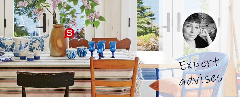 A dining table full of light an colours. Large dining table covered with stripped tablecloth and surrounded by wooden chairs in various styles and sizes. There is a vase with fresh flowers and set of white and blue tableware. In the back there a large windows with some spectacular view.