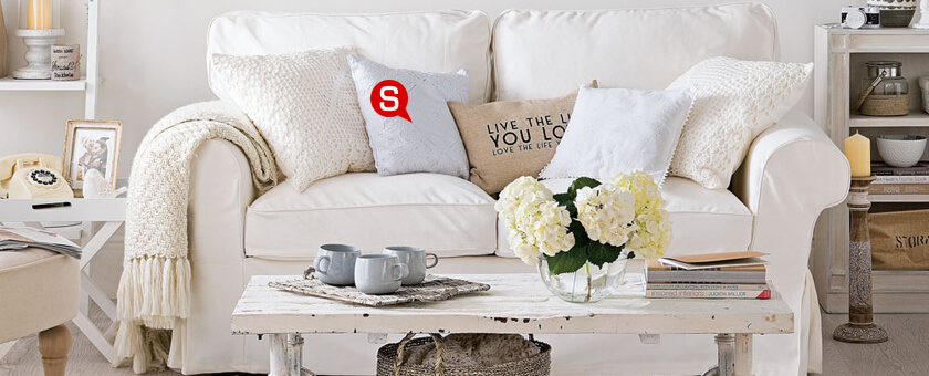 A bright living room in a shabby chic style with a comfortable white sofa, full of decorative throw pillows and a beige blanket. The white coffee table with flowers and wicker elements complete the look.