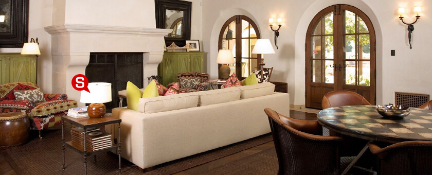 A colonial style living room with a wooden floor and ceiling and an antler wall decor over the fireplace.